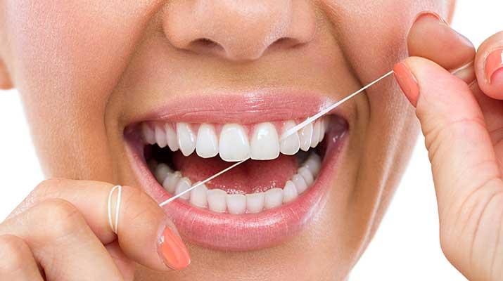 Woman flossing her teeth