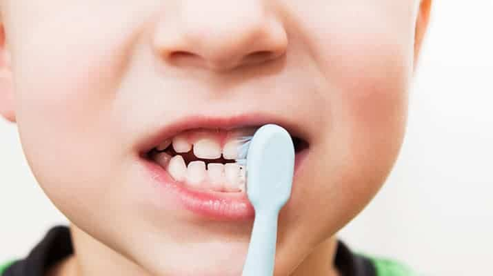 Child brushing his teeth with electric toothbrush