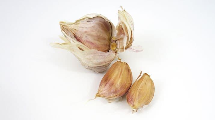 Cloves of garlic next to garlic bulb