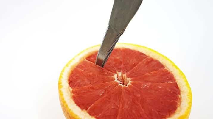 Grapefruit-knife-cutting-down-membrane-of-flesh