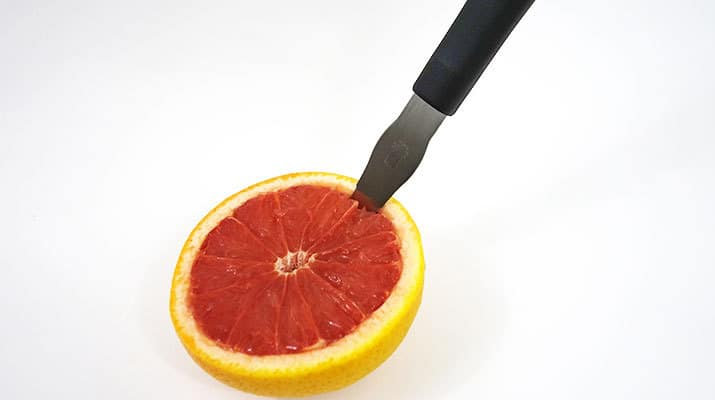 Grapefruit knife slicing around the wall of skin