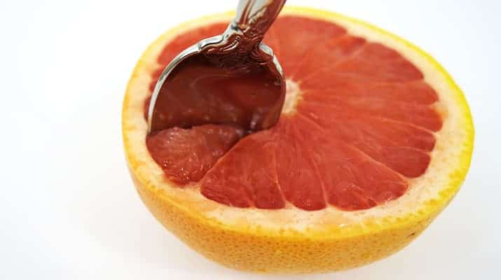 Making a second cut along the membrane spoke of a red grapefruit