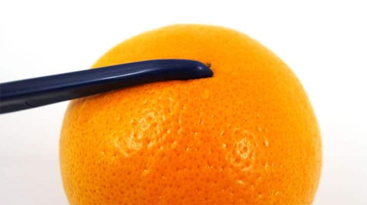piercing the skin of an orange with tupperware citrus peeler