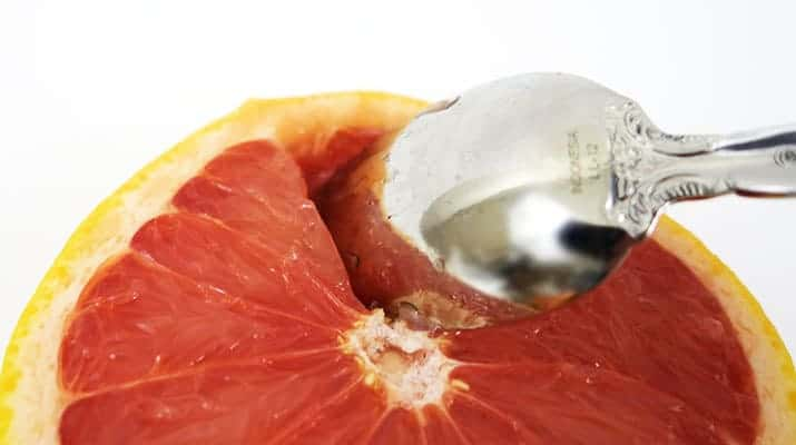 Tearing at the grapefruit membrane with a serrated spoon