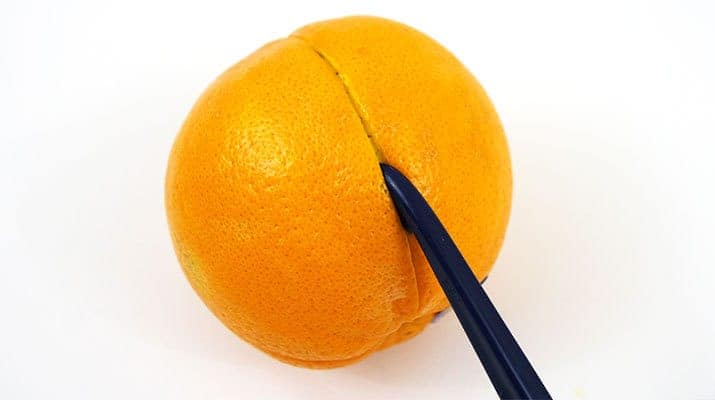 Making a slice in the skin of an orange with tupperware citrus peeler