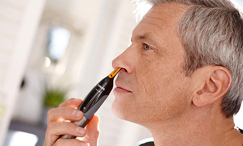 Philips Norelco NoseTrimmer cutting midle aged mans nose hairs