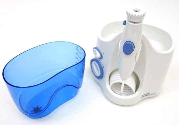 Waterpik Ultra water container sitting beside the Waterpik unit