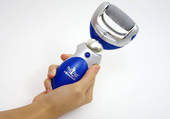 Ped Egg Powerball rechargeable callus remover held in right hand