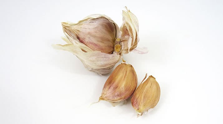 Cloves of garlic next to garlic bulb