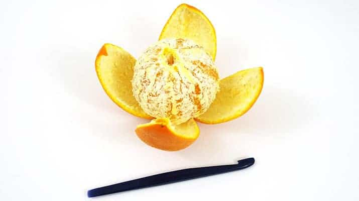 Orange completely peeled with tupperware citrus peeler next to it