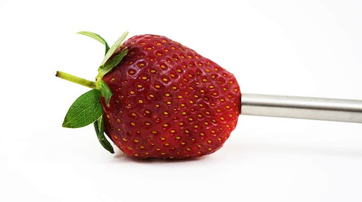 Tovolo strawberry huller pressing against base of strawberry
