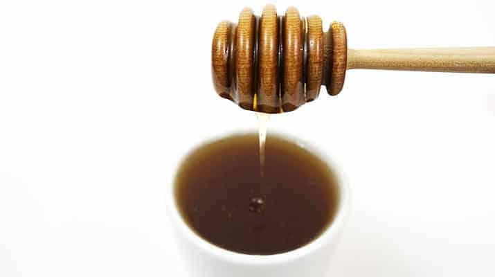Wooden honey wand drizzling honey