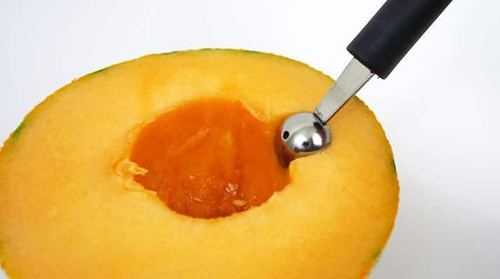 Pushing melon baller scoop into the flesh of cantaloupe melon